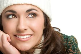 Lady wears white beanie hats smiling and looking up with her chin propped on her hand.