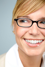 Woman with glasses smiling with healthy teeth